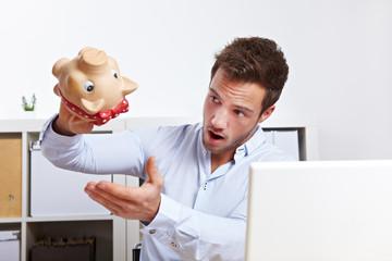 Mann schüttelt leeres Sparschwein