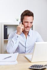Student am Laptop telefoniert mit Handy