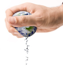 Hand squeezing earth with water drops isolated on white.