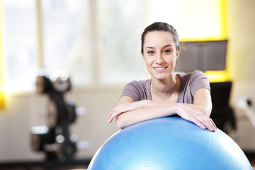 Attractive young woman leaning on an exercise ball at the gym