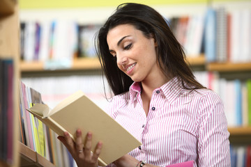 smiling female student reading a book in a bookstore