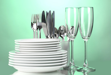 Clean plates, glasses and cutlery on green background