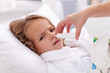 Little girl with bad cold using nasal spray