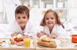 Kids having a healthy breakfast in bed