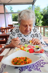 a senior lovely woman eating breakfast