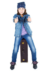 Cute girl sitting on suitcase with thumbs up