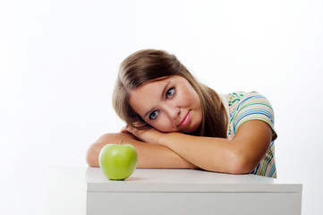 Portrait of a young woman looking at green apple in front of her