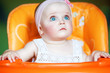 cute baby with blue eyes in orange chair