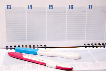 Pregnancy test over calendar
