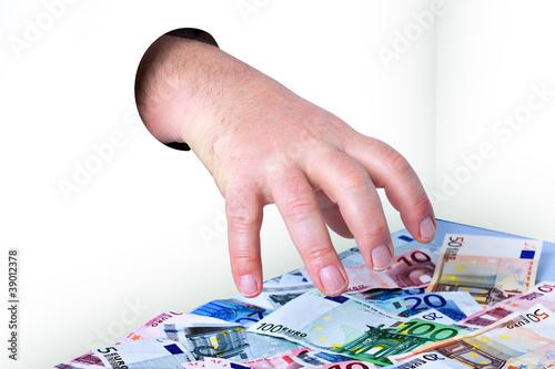 Hand kommt durch das Loch und nimmt Geld