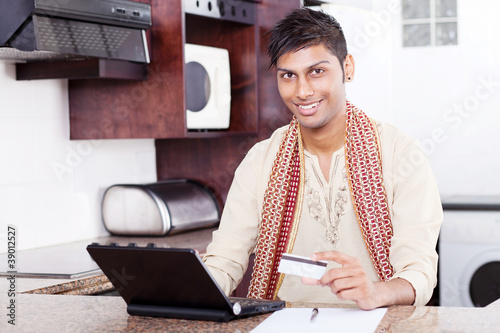 young indian man holding credit card