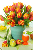 Beautiful bouquet of tulips in vase with Easter eggs.