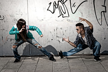 Young urban couple dancers hip hop dancing fight acting urban