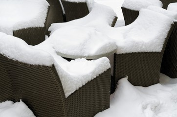 rattan chairs with table covered with snow detail