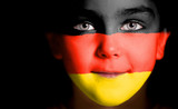 Child face painted with the flag of Germany.