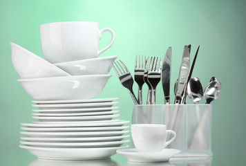 Clean plates, cups and cutlery on green background
