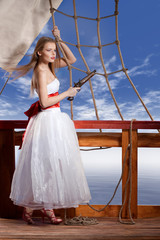 Beautiful girl in white dress on deck of the sailing ship