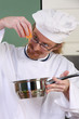 Funny young chef add carrots in the pot