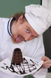 Funny young chef eating a piece of cake