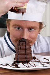 Funny young chef added chocolate sauce at piece of cake