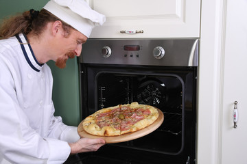 Young chef prepared italian pizza in kitchen