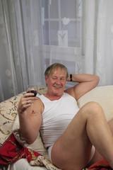 Bestager in Unterwäsche mit einem Glas Rotwein