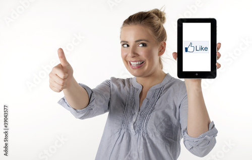 "A pretty young woman showing thumbs up and ""like"" on Tablet PC"