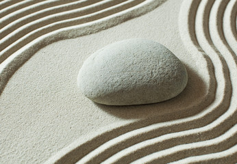 zen pebble isolated on sand