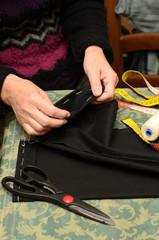 donna cuce l'orlo dei pantaloni