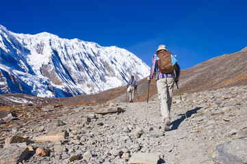 Two trekkers running on the road against Tilicho Lake