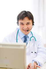 Smiling medical doctor with headset working on pc
