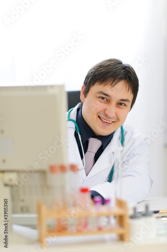 Smiling medical doctor looking out from computer at office