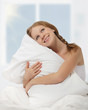 dreamy beauty girl hugging a pillow while sitting in bed