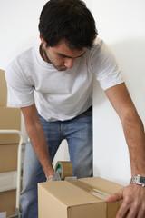 Young man taping shut a cardboard box