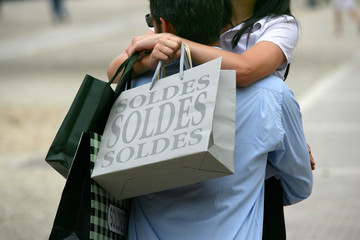 Couple hugging with shopping bags