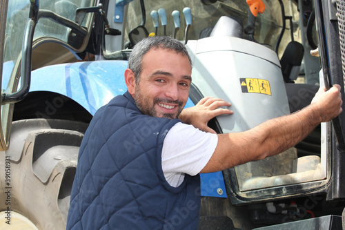portrait of a farmer climbing on tractor