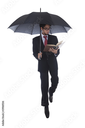 Businessman reading a book under umbrella