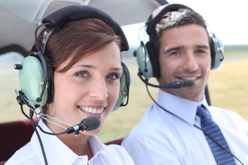 Man and woman wearing headsets in the open cockpit