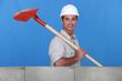 Mason with shovel building wall