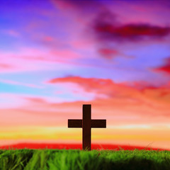 cross silhouette on grass with sunset background