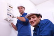 Young electricians with a fusebox