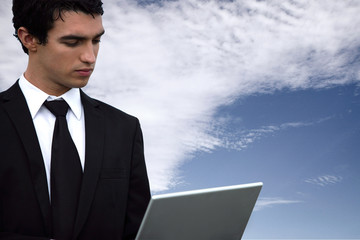 Businessman with a laptop against a blue sky