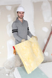 Worker handling square of insulation