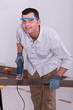 Handyman cutting a piece of wooden flooring