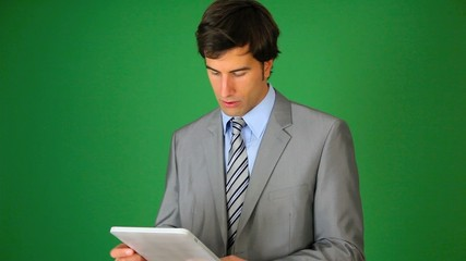 Businessman standing on green background wth tablet