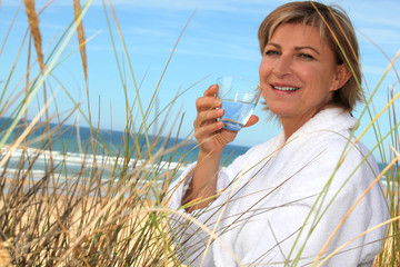 Woman drinking a glass of water by the seaside