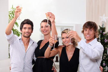 Two young couples drinking champagne at Christmas