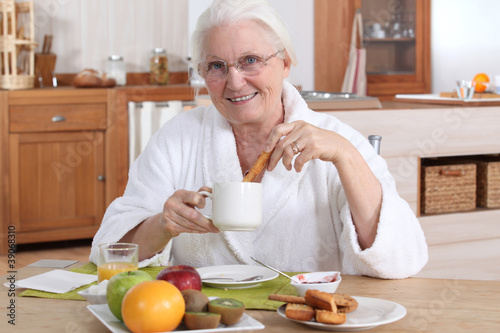 A mature woman having breakfast.