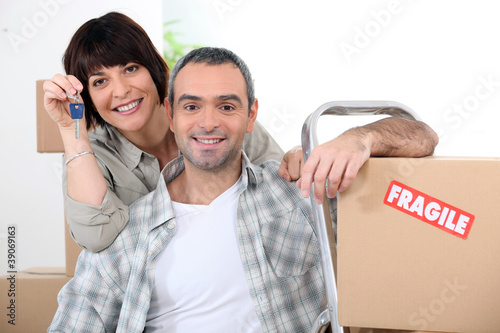 Couple moving into new home with doorkeys and boxes