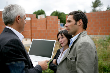 Young couple and entrepreneur on a site under construction